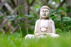 Pequeña estatua blanca de Buda en una actitud de la meditación con primero plano de la hierba verde y en fondo borroso brillante  imagen de archivo