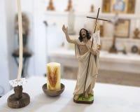 Pequeña estatua de Jesús y de dos velas en una pequeña iglesia en Masseria IL Frantoio, Italia meridional imagenes de archivo