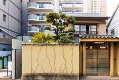 Pequeña fachada japonesa vieja de la casa en el fondo de altos edificios residenciales en Japón fotos de archivo