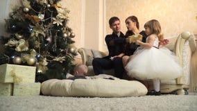 Pequeña familia feliz en el sofá el Nochebuena almacen de video