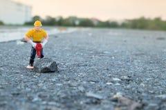 Pequeña figura de un hombre que cava el camino concreto Imagenes de archivo