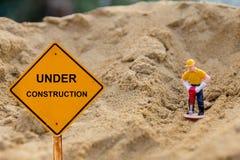 Pequeña figura de una tierra de excavación del hombre con el mensaje inferior de la construcción Foto de archivo