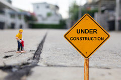 Pequeña figura que cava la calle concreta con el mensaje inferior de la construcción Fotos de archivo
