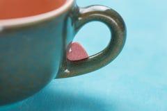 Pequeña forma rosada Sugar Candy del corazón en la manija de la taza de té del café en fondo azul claro valentines imagen de archivo libre de regalías