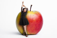 Pequeña hembra que permanece cerca de manzana gigante; mujer en dieta, Fotos de archivo