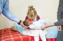Pequeña hermana que abraza y que besa a su hermano del bebé imágenes de archivo libres de regalías