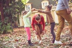 Pequeña hermana que juega con los padres en el patio trasero Foto de archivo libre de regalías