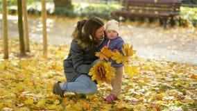 Pequeña hija feliz de la familia, de la madre y del niño que juega y que sostiene las hojas, abrazo de risa en Autumn Walk en nat metrajes