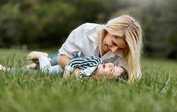 Pequeña hija feliz que miente en la hierba verde y que juega con su madre sonriente en el parque Mujer de amor y su niño foto de archivo libre de regalías
