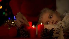 Pequeña hija que mira cómo madre que enciende las velas de la Navidad, creencia en milagro imagen de archivo libre de regalías