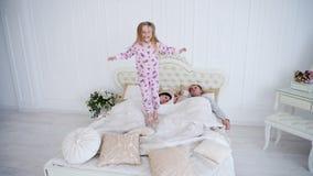 Pequeña hija que salta y que engaña en cama mientras que el dormir de los padres imagen de archivo