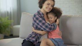 Pequeña hija que se acurruca firmemente a la madre, a la plena confianza y al afecto queridos almacen de video