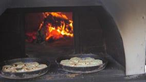 Pequeña hornada de la pizza en el fuego ardiente del horno vídeo de la cámara lenta el cocinero prepara forma de vida de los past metrajes