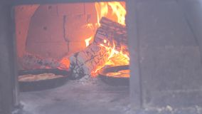 Pequeña hornada de la pizza en el fuego ardiente del horno vídeo de la cámara lenta el cocinero prepara los pasteles en un fuego  almacen de video