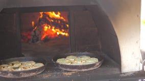 Pequeña hornada de la pizza en el fuego ardiente del horno vídeo de la cámara lenta la forma de vida el cocinero prepara los past almacen de video