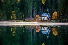 Pequeña iglesia en el lago Braies del italiano con reflexiones imagenes de archivo
