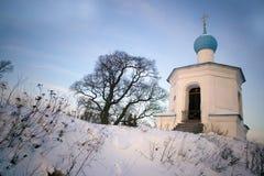 Pequeña iglesia ortodoxa en una colina nevada foto de archivo libre de regalías
