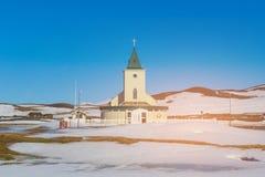 Pequeña iglesia sobre nieve en la tierra con el cielo azul claro Imagen de archivo