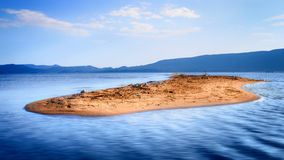 Pequeña isla arenosa solitaria en el medio del mar azul Fotografía de archivo libre de regalías