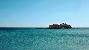 Pequeña isla con una casa rodeada por un mar tranquilo y apacible del golfo de la turquesa sobre un cielo azul del verano metrajes