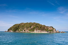 Pequeña isla en el medio del mar y del cielo azul imagen de archivo