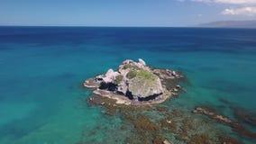 Pequeña isla que sorprende cerca de la costa de piedra del mar tropical caliente, visión aérea almacen de video