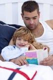 Pequeña lectura del hijo con su padre en cama Imagen de archivo