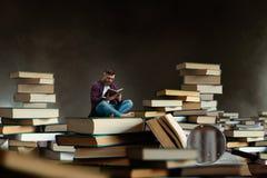 Pequeña lectura del hombre entre los libros y los libros de texto grandes Imagen de archivo