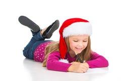 Pequeña letra rubia hermosa de la escritura de la muchacha a Santa Claus. imagenes de archivo