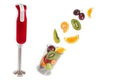 Pequeña licuadora eléctrica y frutas frescas Foto de archivo