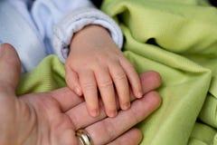 Pequeña mano del bebé en mano de las madres Foto de archivo