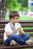 Pequeña mano sonriente del muchacho del niño que sostiene el teléfono móvil o el smartphone Fotos de archivo