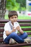 Pequeña mano sonriente del muchacho del niño que sostiene el teléfono móvil o el smartphone Imagenes de archivo