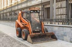 Pequeña maquinaria anaranjada de la niveladora usada para limpiar por municipali Imagenes de archivo
