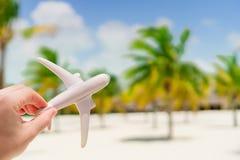 Pequeña miniatura blanca de un aeroplano en el fondo de la playa y de palmtrees exóticos Imágenes de archivo libres de regalías