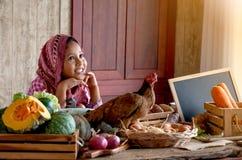 Pequeña mirada asiática de la chica joven adelante y sonrisa entre diversos tipos de verdura en la tabla en su cocina imagen de archivo libre de regalías