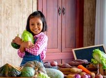 Pequeña mirada asiática de la chica joven adelante y sonrisa entre diversos tipos de verdura en la tabla en su cocina con felicid imagen de archivo libre de regalías