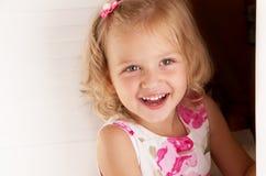 Pequeña mirada rubia de la muchacha fuera de la puerta Foto de archivo libre de regalías