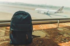 Pequeña mochila azul que se coloca en el piso en el aeropuerto imagenes de archivo