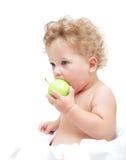 Pequeña mordedura de pelo rizado del niño de una manzana verde Imagen de archivo