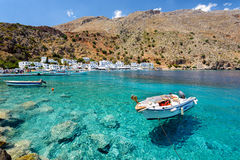Pequeña motora en la bahía clara del agua de la ciudad de Loutro en la isla de Creta, Grecia imagen de archivo