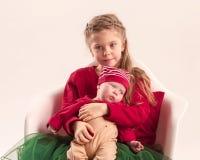 Pequeña muchacha adolescente feliz que detiene a su pequeña hermana del bebé recién nacido Amor de la familia Foto de archivo libre de regalías