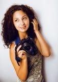 Pequeña muchacha adolescente linda del inconformista con el pelo rizado que sostiene la cámara, fotógrafo que toma un tiro, conce Imágenes de archivo libres de regalías