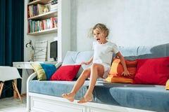 Pequeña muchacha adolescente sorprendida que ve la TV en casa Foto de archivo