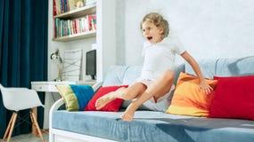 Pequeña muchacha adolescente sorprendida que ve la TV en casa Imagen de archivo libre de regalías