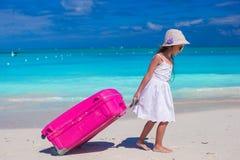 Pequeña muchacha adorable con equipaje grande en manos encendido Foto de archivo libre de regalías