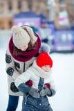 Pequeña muchacha adorable con su madre que patina en hielo-pista Fotos de archivo