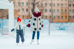 Pequeña muchacha adorable con su madre que patina en hielo-pista Foto de archivo libre de regalías