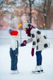 Pequeña muchacha adorable con su mamá que patina en hielo-pista Fotos de archivo