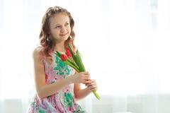 Pequeña muchacha adorable del adolescente que se sienta en la ventana y que sostiene tulipanes Imagen de archivo